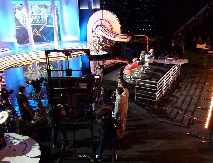 За спинами жюри, возле экрана телесуфлёра, откуда читают свои реплики ведущие (вдалеке в средней части кадра), ожидают выхода на сцену конкурсанты-трубачи