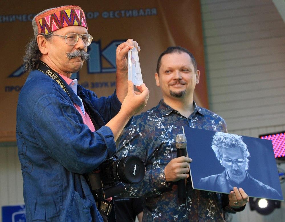Август 2012: Павел Корбут получает премию Jazz Award от Международной ассоциации джазовых журналистов. Редактор «Джаз.Ру» Кирилл Мошков держит в руках работу, за которую российский фотограф был удостоен международной награды.