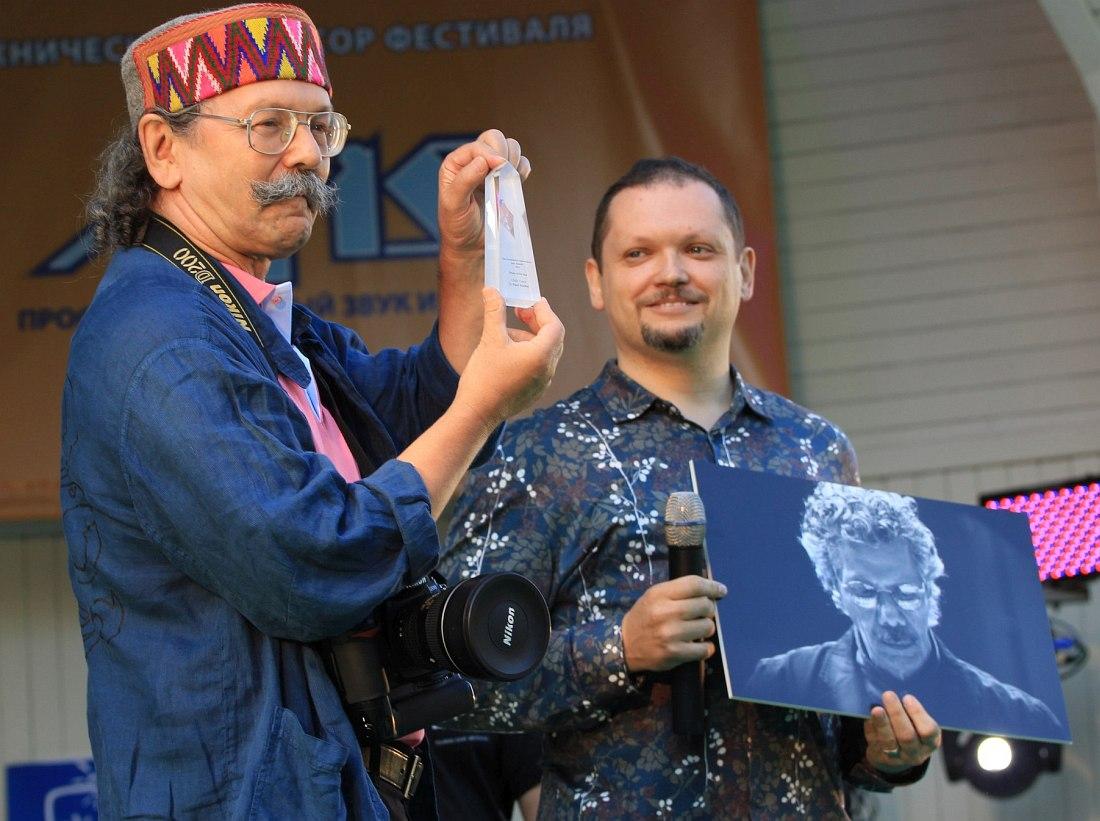 Главный редактор «Джаз.Ру» Кирилл Мошков (справа) на сцене фестиваля «Джаз в саду Эрмитаж-2012» держит в руках фотографию, за которую Павел Корбут (слева) получил Jazz Award. Награду для Павла (он держит её в руках) привезли из Нью-Йорка.