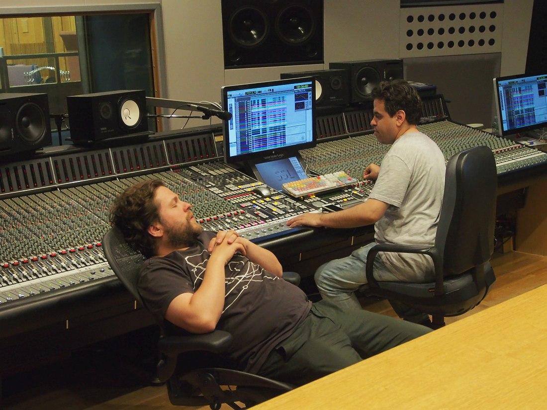Пока звукорежиссёр Андрей Левин воспроизводит музыкантам только что записанный материал, барабанщик Пётр Ившин внимательно прислушивается к тонкостям партии ударных