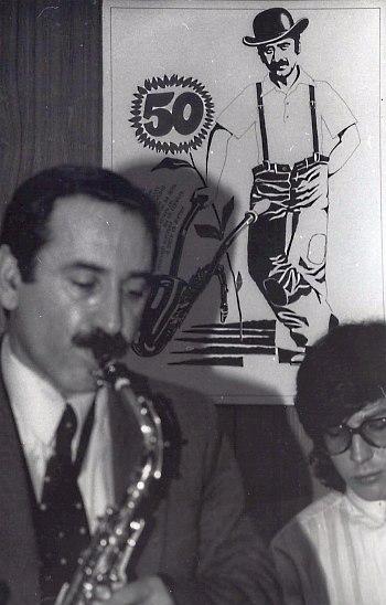 1988: Геннадий Гольштейн отмечает 50-летие. На заднем плане шарж Влада Панкевича, представляющий Гольштейна в образе «Чарли». Фото © Александр Смирнова