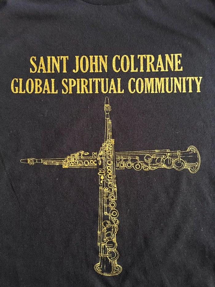 На сайте Церкви Колтрейна можно купить, например, такую футболку. Надпись гласит «Всемирное духовное сообщество святого Джона Колтрейна».