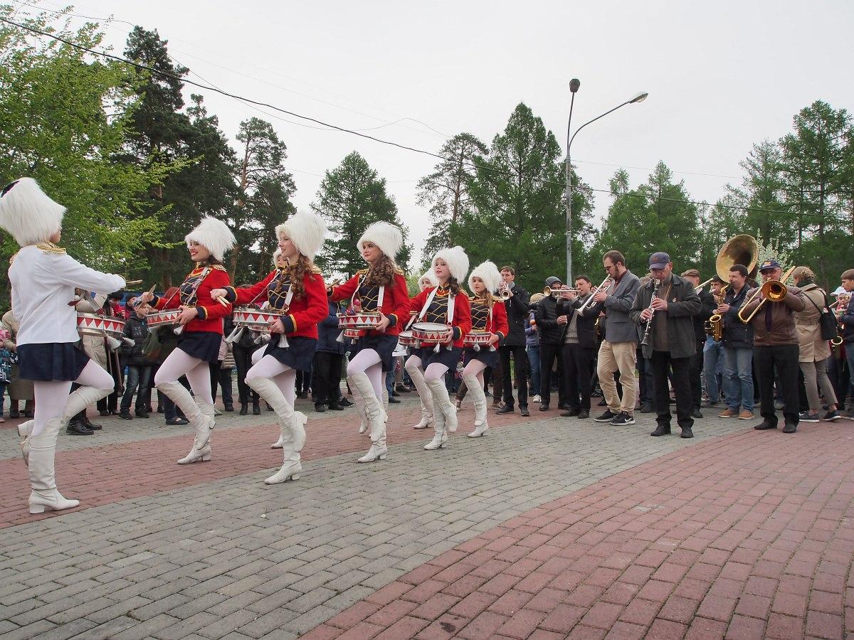 Участники фестиваля позади колонны мажореток в тёплых рейтузиках идут традиционным диксилендовым парадом к сцене гала-концерта