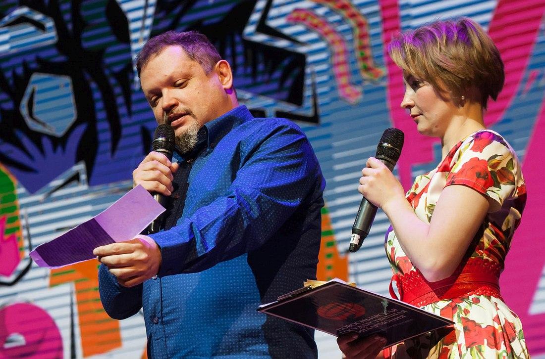 Автор текста зачитывает вопросы со сцены (справа ведущая детского концерта Дарья Нехаева). Фото © Михаил Афанасьев
