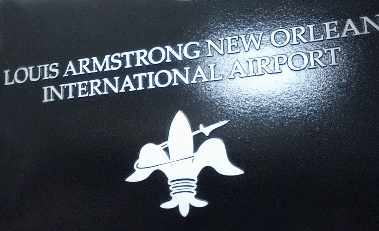 Вывеска Нью-Орлеанского международного аэропорта им. Луи Армстронга. В эмблеме силуэт реактивного самолёта соединён с геральдическим символом Орлеанского дома — лилией.