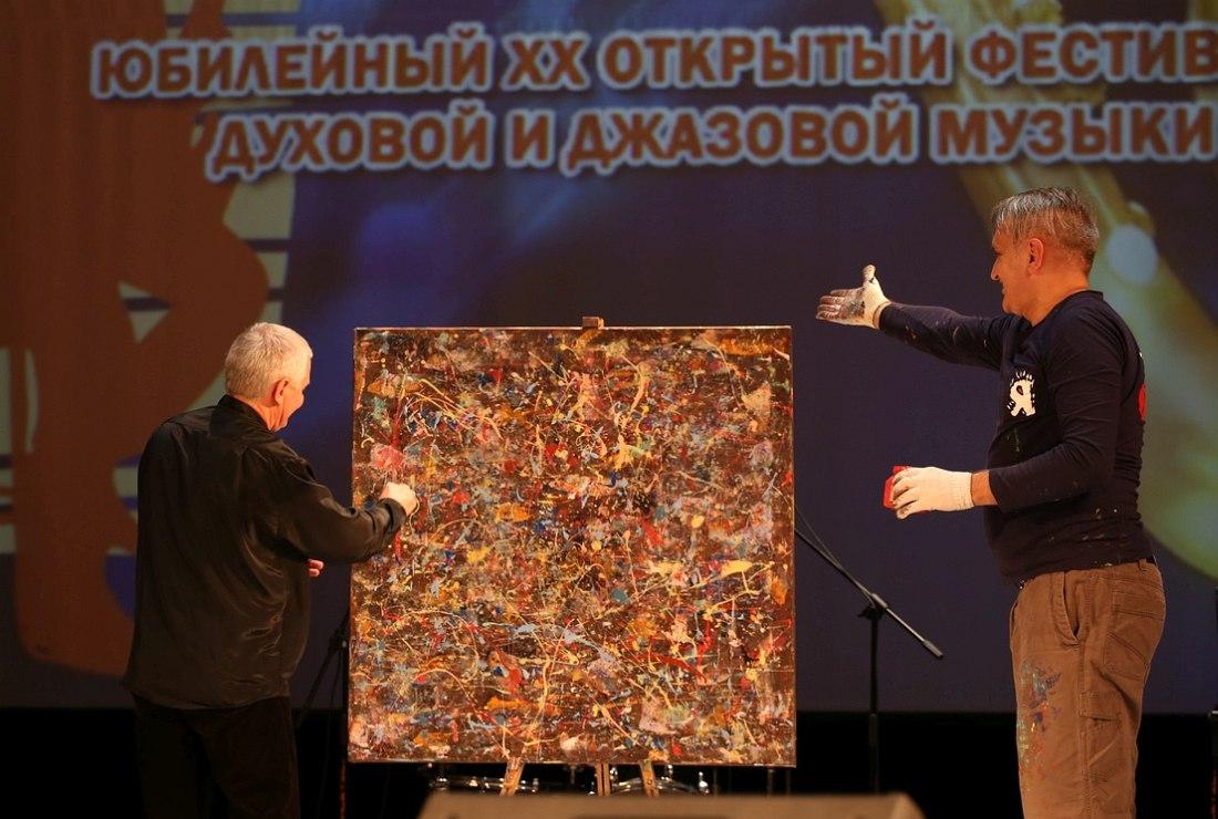 Игорь Володин наносит финальный мазок на холст, над которым во время его выступления трудился на сцене «антихудожник» из Нижнего Новгорода Стос Карпов (справа)