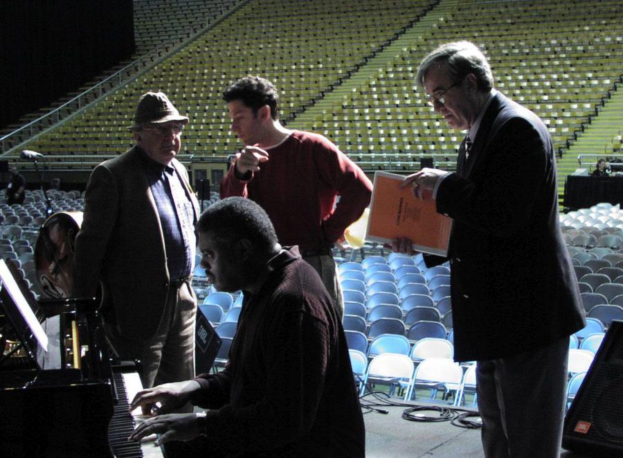 Февраль 2002, сцена стадиона Kibbie Dome в Москоу, Айдахо. Док Скиннер (справа) на репетиции и саундчеке «хауз-бэнда» (основной ритм-секции) фестиваля. За роялем Малгру Миллер (1955-2013), за ним гитарист Бакки Пиццарелли(1926-2020) и его сын, певец и гитарист Джон Пиццарелли (фото © Кирилл Мошков, «Джаз.Ру»)