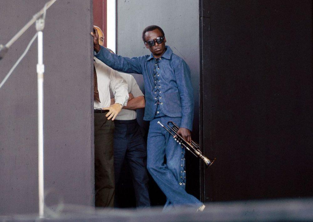Майлз Дэйвис в кулисе фестиваля в Ньюпорте, лето 1969. Из-за его руки выглядывает Джордж Уэйн (фото © David Redfern)